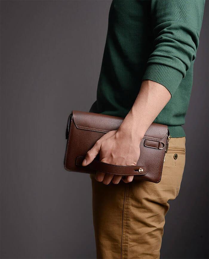 Cầm ví cầm tay và tạo dáng sát hông